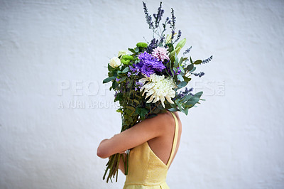 Buy stock photo Studio shot of an unrecognizable woman holding a bouquet of flowers while standing against a grey background