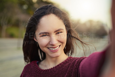 Buy stock photo Portrait of a happy young woman taking a selfie outdoors
