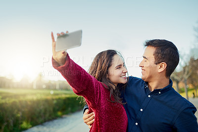 Buy stock photo Shot of a happy young couple taking a selfie outdoors