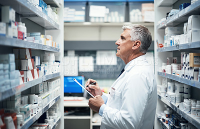 Buy stock photo Cropped shot of a mature male pharmacist doing stock take while working in a dispensary