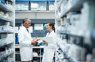 Buy stock photo Cropped shot of two pharmacists doing stock take while working together in a dispensary