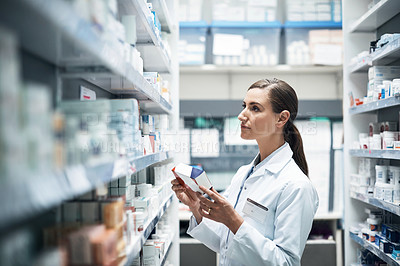 Buy stock photo Cropped shot of a young female pharmacist checking products while working in a dispensary