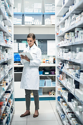 Buy stock photo Full length shot of a young female pharmacist doing stock take while working in a dispensary