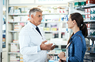 Buy stock photo Shot of a mature pharmacist assisting a young woman in a chemist