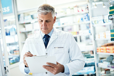 Buy stock photo Shot of a mature pharmacist making notes on a clipboard in a pharmacy