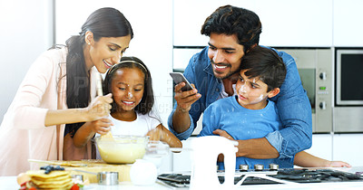 Buy stock photo Shot of a young family making pancakes together in the kitchen at home