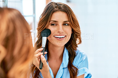 Buy stock photo Cropped shot of a beautiful young woman applying blush on to her cheeks at home