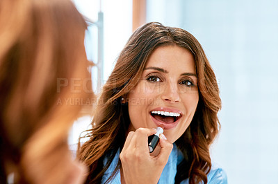 Buy stock photo Cropped shot of a beautiful young woman applying lipstick at home