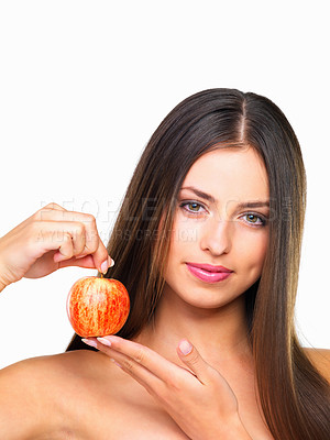 Buy stock photo Studio portrait of a beautiful young woman eating an apple against a white background
