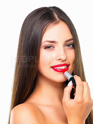 Buy stock photo Studio portrait of a beautiful young woman applying red lipstick against a white background