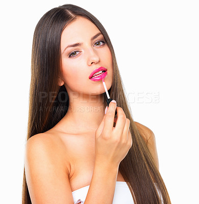 Buy stock photo Studio portrait of a beautiful young woman applying pink lip gloss against a white background