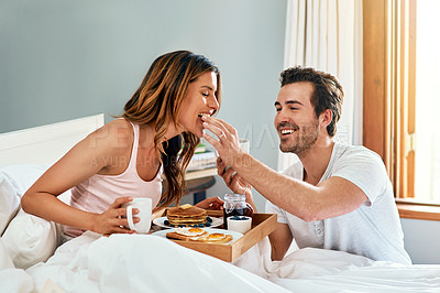 Buy stock photo Shot of a happy young couple enjoying breakfast in bed together at home