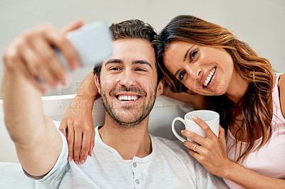 Buy stock photo Shot of a happy young couple taking a selfie together at home