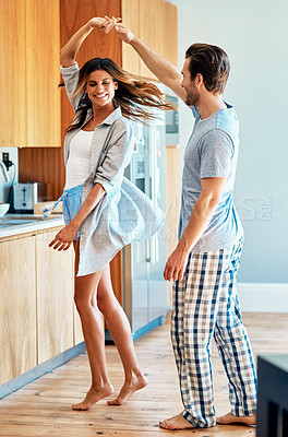 Buy stock photo Shot of a happy young couple dancing together at home
