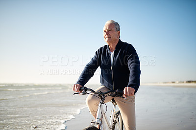 Buy stock photo Shot of a senior man riding a bicycle at the beach