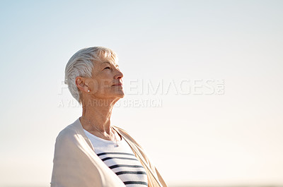 Buy stock photo Shot of a senior woman spending a day at the beach
