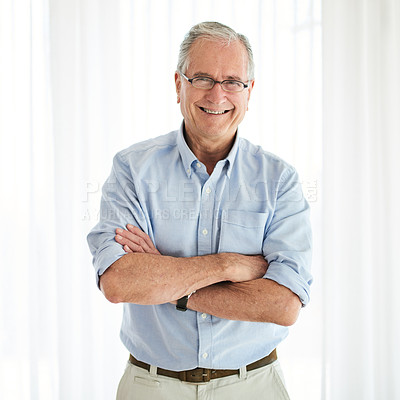 Buy stock photo Shot of a senior man standing confidently with his arms crossed at home