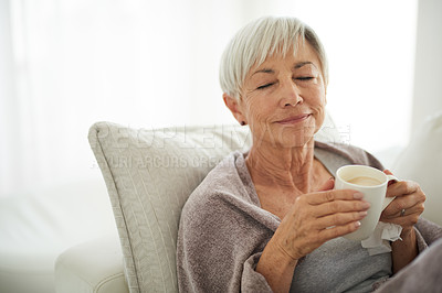 Buy stock photo Shot of a senior woman enjoying a relaxing coffee break on the sofa at home