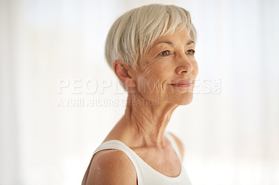 Buy stock photo Shot of a senior woman looking thoughtful at home