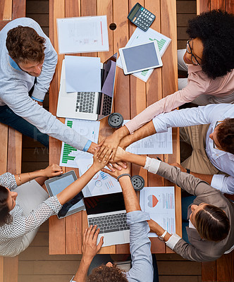Buy stock photo High angle shot of a group of businesspeople joining their hands in a huddle during a meeting outdoors