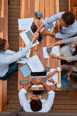 Buy stock photo High angle shot of businesspeople shaking hands during a meeting outdoors