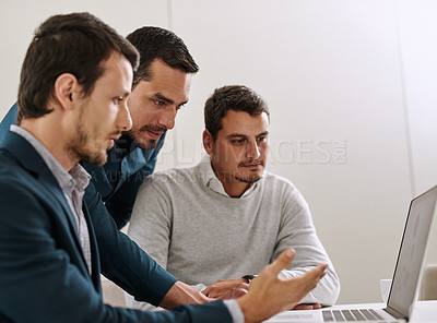 Buy stock photo Shot of a group of businessmen working together on a laptop in an office