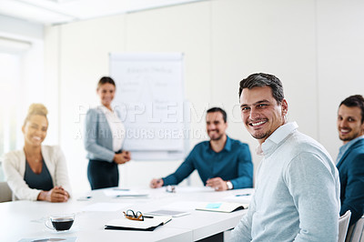 Buy stock photo Portrait of a young businessman having a meeting with his colleagues in an office