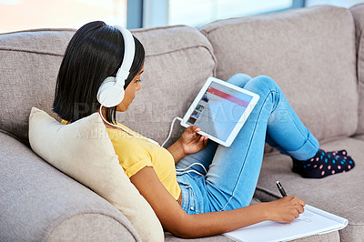 Buy stock photo Shot of a teenage girl listening to music and using a tablet at home