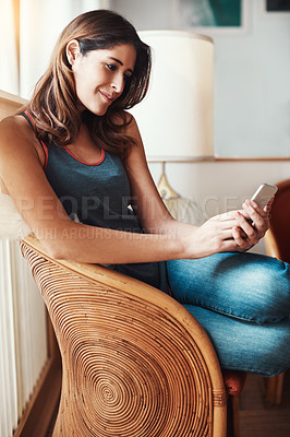 Buy stock photo Shot of an attractive young woman using her cellphone at home