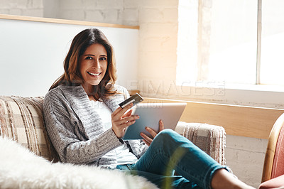 Buy stock photo Portrait of an attractive young woman using a digital tablet and credit card on the sofa at home