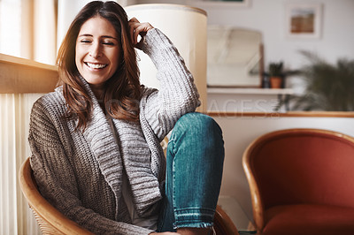 Buy stock photo Shot of an attractive young woman relaxing on a chair at home