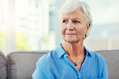 Buy stock photo Cropped shot of a senior woman sitting on her sofa at home