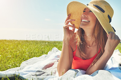 Buy stock photo Shot of a cheerful young woman wearing a hat while lying on a grass field outside in the sun