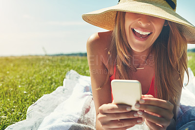 Buy stock photo Shot of a cheerful young woman wearing a hat while lying on the ground busy with her phone outside in the sun