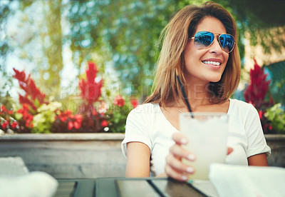 Buy stock photo Shot of a cheerful young woman wearing sunglasses and enjoying a cold beverage while being seated at a restaurant outside during the day