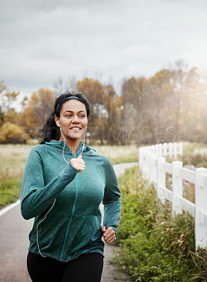 Buy stock photo Shot of an attractive young woman going for a run in nature