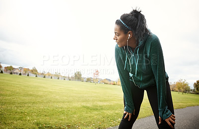 Buy stock photo Shot of an attractive young woman taking a break while out for a run in nature