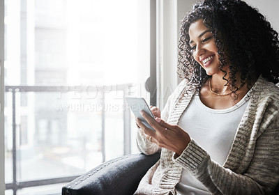 Buy stock photo Shot of a cheerful young woman relaxing while texting on her cellphone at home during the day