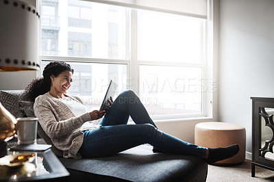 Buy stock photo Shot of a cheerful young woman relaxing on a chair while browsing on a digital tablet at home