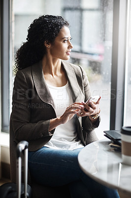 Buy stock photo Shot of a young businesswoman using a cellphone while waiting for her flight in an airport lounge