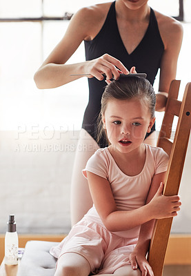 Buy stock photo Shot of an adorable little girl getting her hair tied up by an older girl in a ballet studio