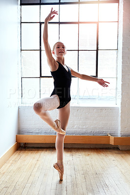 Buy stock photo Shot of a young girl practicing ballet in a dance studio