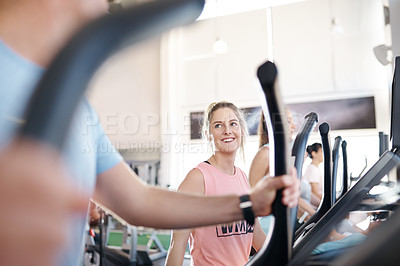 Buy stock photo Shot of a man and woman talking while exercising on treadmills in a gym