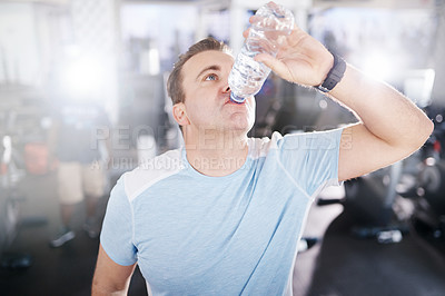 Buy stock photo Shot of a mature man drinking water while exercising in a gym