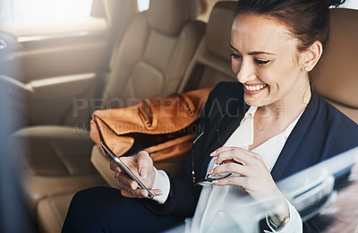 Buy stock photo Shot of a confident young businesswoman seated in a car as a passenger while texting on her phone on her way to work