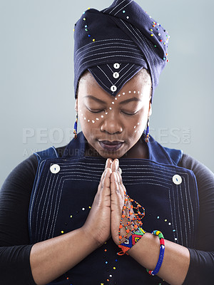 Buy stock photo Studio shot a confident middle aged woman holding her hands together and praying while standing against a grey background