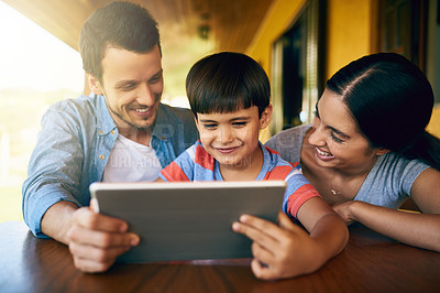 Buy stock photo Cropped shot of an affectionate young family using a tablet together at home