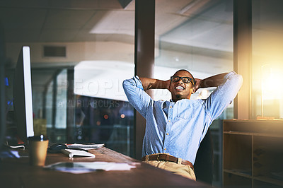 Buy stock photo Shot of a young businessman relaxing at his desk during a late night at work
