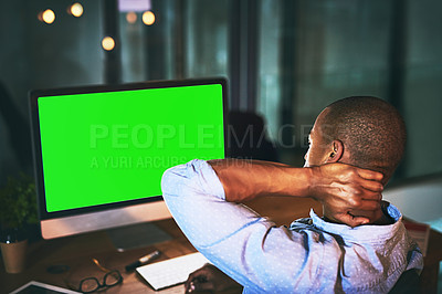 Buy stock photo Shot of a young businessman experiencing tension while using a computer with a green screen late at work