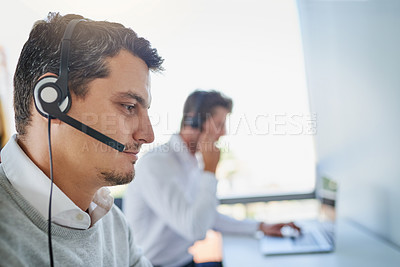 Buy stock photo Shot of a young call centre agent working in an office with his colleagues in the background